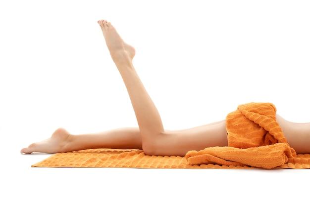 Gambe lunghe di donna rilassata con un asciugamano arancione su bianco