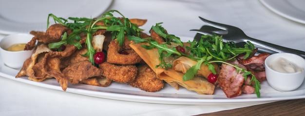 Piatto ovale lungo con varietà di snack: patatine, nachos, bacon, lavash con formaggio, rucola, mirtilli rossi, anelli di calamaro o cipolle impanate. banner