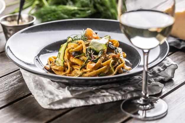Pasta lunga con salmone affumicato e zucchine servite su un piatto scuro accanto a un bicchiere di vino bianco.
