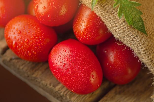 Pomodori prugna lunghi sulla tavola di legno. cumulo di pomodori freschi in sacchetto di tela ruvida sul tavolo di legno. concetto di prodotto naturale.