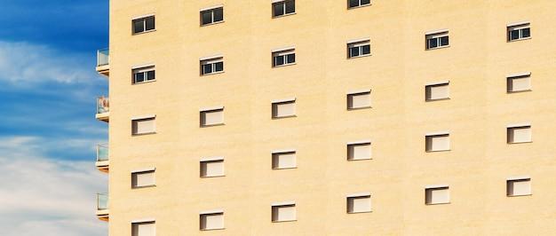 Lungo edificio residenziale con un motivo ripetuto nel muro di mattoni, con cielo blu sullo sfondo