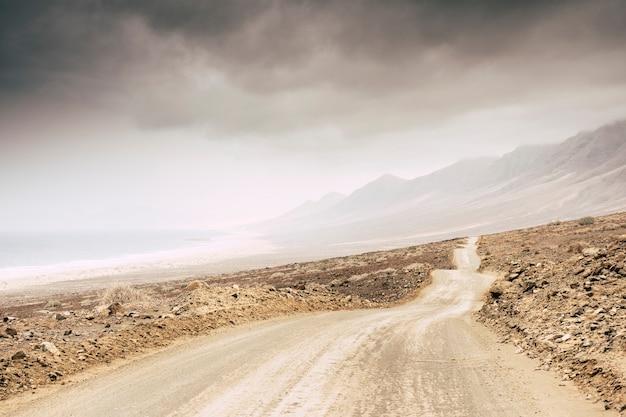 Lunga strada senza asfalto solo terra e rocce nel mezzo di un deserto di lava a fuerteventura. viaggia e scopri il mondo per una vacanza o un'avventura alternativa