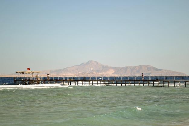 Un lungo molo che va in mare, le persone non sono su di esso e la bandiera vieta il nuoto. sullo sfondo ci sono le montagne. mare di due colori