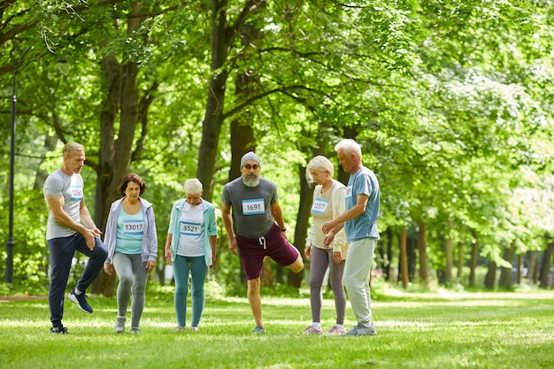 Campo lungo di anziani attivi che prendono parte alla gara di maratona estiva che stanno insieme da qualche parte nel parco facendo esercizio di stretching