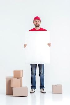 Colpo lungo del corriere circondato da scatole in possesso di un bordo vuoto