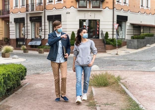 Amici dal tiro lungo che camminano e chiacchierano mentre indossano maschere mediche