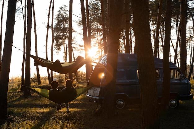 Amici a tiro lungo con amache al tramonto