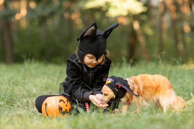 Colpo lungo del ragazzino in costume da pipistrello e cane