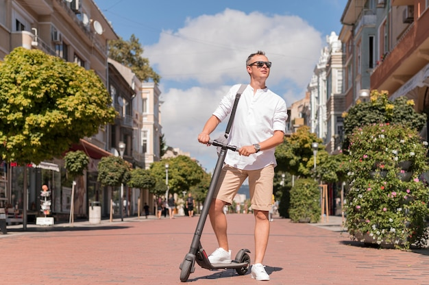 Uomo moderno di tiro lungo su scooter all'aperto