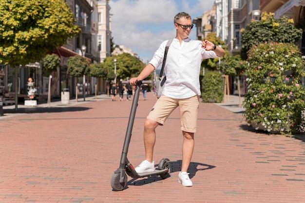 Uomo moderno di tiro lungo su scooter