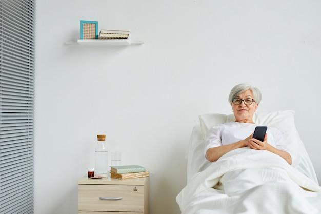 Colpo lungo di senior donna che indossa abiti bianchi rilassante sul letto in ospedale utilizzando il suo smartphone