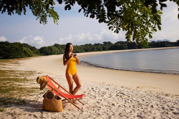 Donna lunga in spiaggia con la macchina fotografica