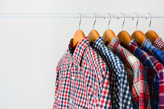 La camicia a quadretti a maniche lunghe sul gancio di legno appende sullo scaffale dei vestiti sopra fondo bianco