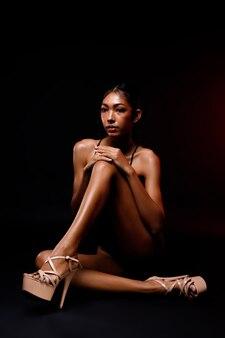 Gambe lunghe e sottili con un bel dito della pelle e la forma di una donna asiatica con la pelle abbronzata degli anni '20. modello femminile per scarpe con tacco alto e prodotti per collant su un'area di luce selettiva su sfondo nero