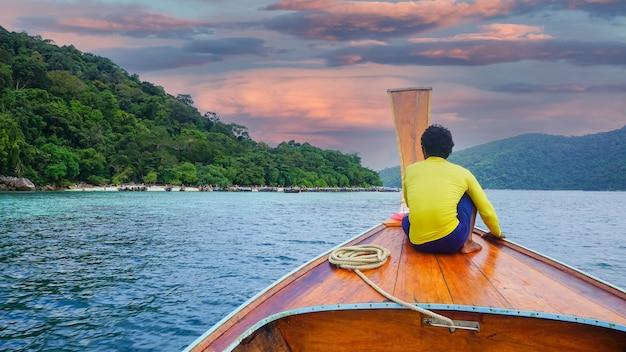 Barche a coda lunga con montagne di acqua cristallina e cielo blu brillante a koh lipe in thailandia