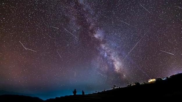 Paesaggio notturno di lunga esposizione con la via lattea durante la pioggia di meteoriti su una montagna con capanna.