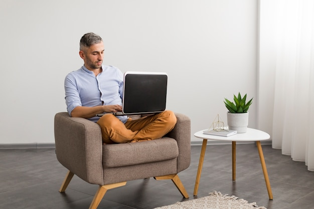 Uomo di vista lunga che per mezzo del suo computer portatile all'interno