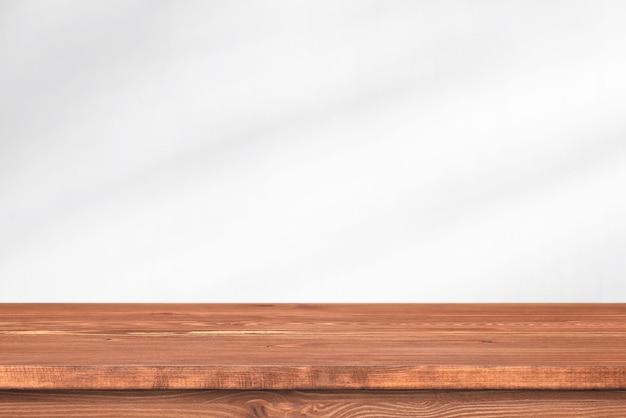 Lungo tavolo in legno davanti al muro con luce soffusa. scrivania vuota, scaffale o piano del tavolo per il modello.