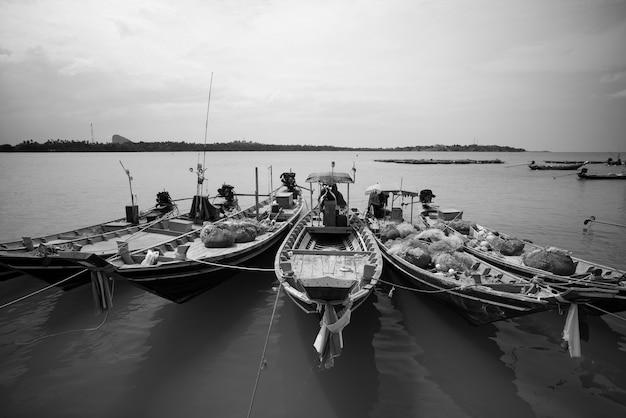 Barche da pesca a coda lunga al villaggio di pescatori in thailandia in bianco e nero.