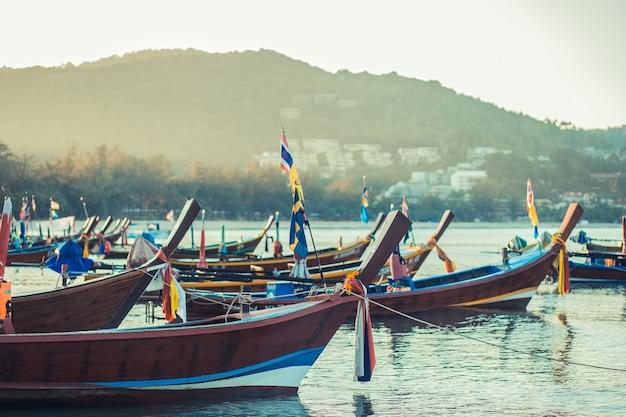 Barca di longtale alla spiaggia tailandese. posto sulla spiaggia di sabbia paradice. barche sull'acqua limpida e sul cielo blu di alba.
