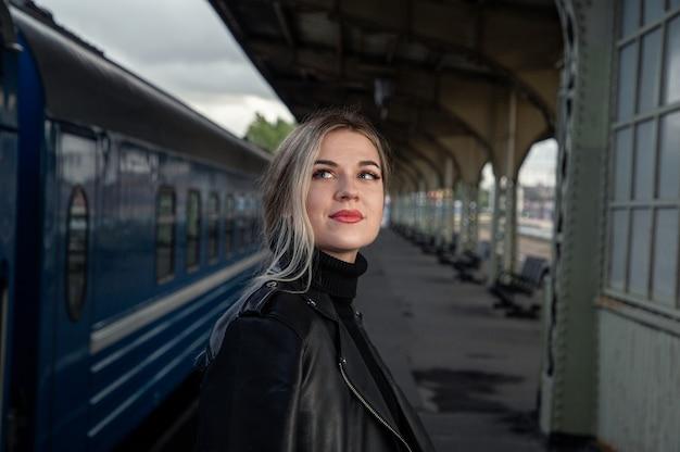 Sguardo di una bella ragazza alla stazione dei treni perone