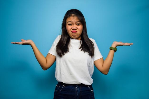Guarda la telecamera e crea donne confuse e asiatiche usando una maglietta bianca isolata sul blu
