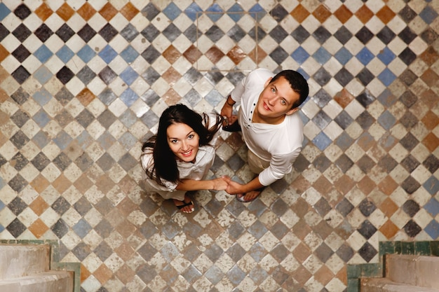 Osservi dall'alto la coppia adorabile che sta sul cortile di una vecchia casa marocchina