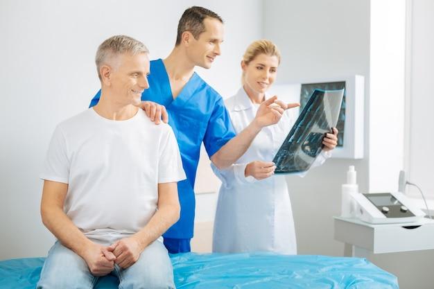 Guarda qui. felice allegro terapista maschio che tiene la spalla dei suoi pazienti e indica l'immagine a raggi x mentre lavora con il suo collega