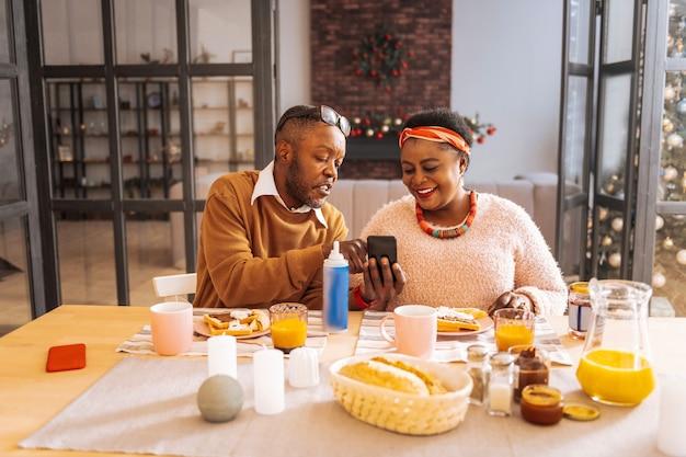 Guarda qui. piacevole uomo simpatico che indica lo schermo del suo smartphone mentre mostra un'immagine interessante a sua moglie