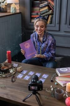 Guarda qui. bella donna positiva che sorride mostrando un libro sull'esoterismo mentre è seduto davanti alla telecamera