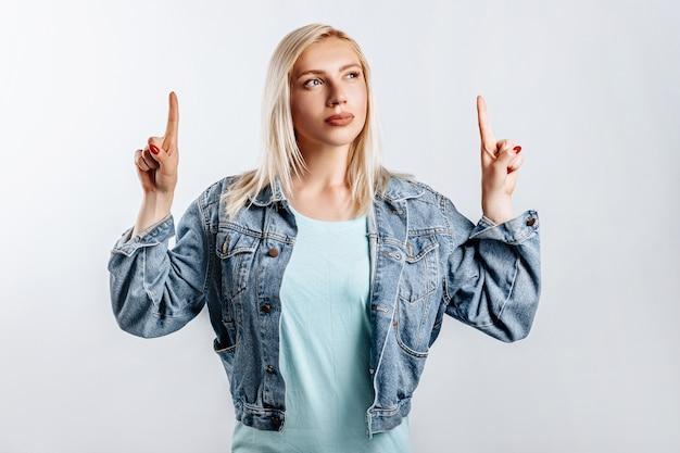 Guarda qui. la giovane bella donna bionda punta le dita verso l'alto pensa e prende una decisione. la donna ha pensato alla scelta. posto per la pubblicità.