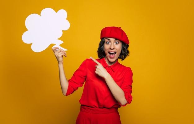 Guarda! ho un'idea! giovane turista, vestita in stile parigino, con abito rosso e berretto rosso, entusiasta di un'idea sul suo viaggio.