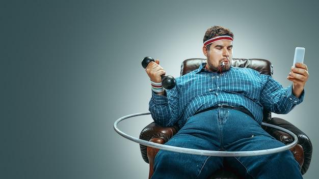 Guarda, sto diventando sportivo. ritratto di uomo caucasico grasso seduto in una poltrona marrone su sfondo grigio. fare selfie con pesi da allenamento e cerchio. sovrappeso, spensierato. concetto di perdita di peso.