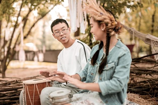 Guardami. incredibile ragazza bruna che suona la batteria mentre si gode la musica nazionale