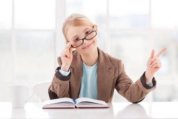 Guarda quello! bambina allegra con gli occhiali e abiti da cerimonia seduta al tavolo e che indica lontano