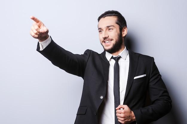 Guarda quello! sorridente giovane in abiti da cerimonia che punta lontano mentre in piedi su sfondo grigio