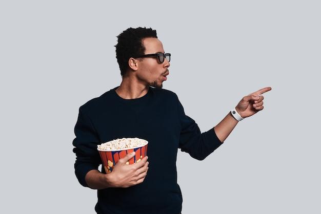 Guarda là! bel giovane in abbigliamento casual che mangia popcorn e indica lo spazio della copia mentre sta in piedi su uno sfondo grigio