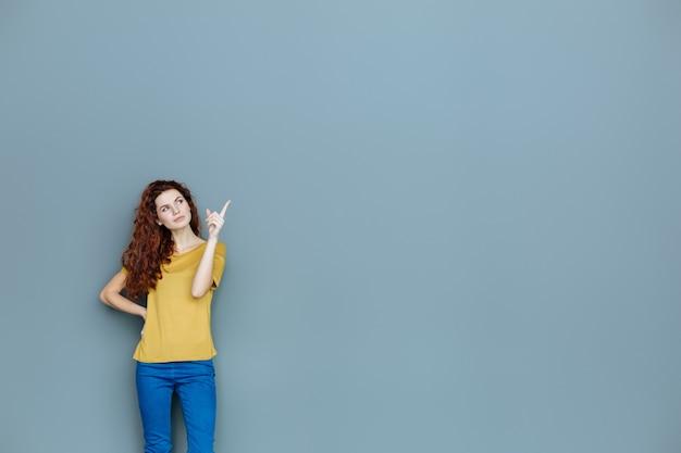 Guarda qui. smart bella donna felice in piedi sullo sfondo e indicando con il dito pur essendo di ottimo umore