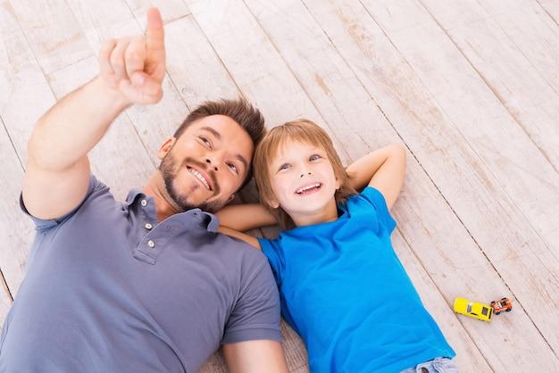 Guarda là! vista dall'alto di padre e figlio felici sdraiati insieme sul pavimento di legno duro mentre il giovane indica e sorride