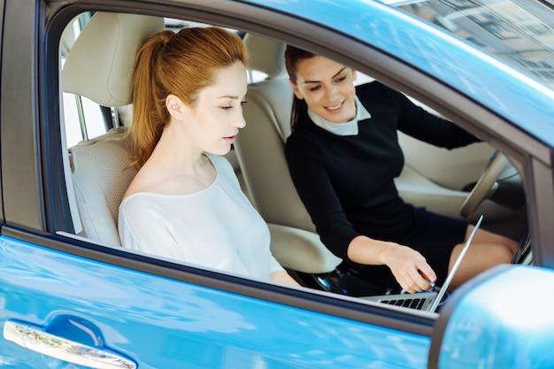 Guarda questo. attraente donna allegra felice sorridendo e indicando lo schermo del laptop mentre era seduto al volante