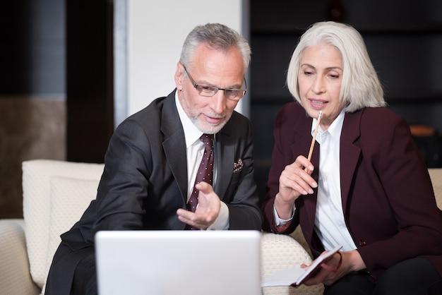 Guarda questo. felice imprenditore invecchiato coinvolto sorridente e seduto in ufficio davanti al computer portatile mentre lavorava con il suo collega e condivideva idee