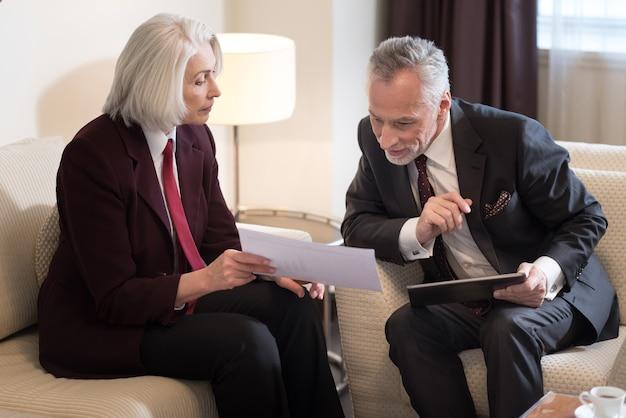 Guarda questo. imprenditrice invecchiata seria coinvolta che tiene le carte mentre era seduto in ufficio vicino al suo collega con il tablet e lavorava insieme al progetto