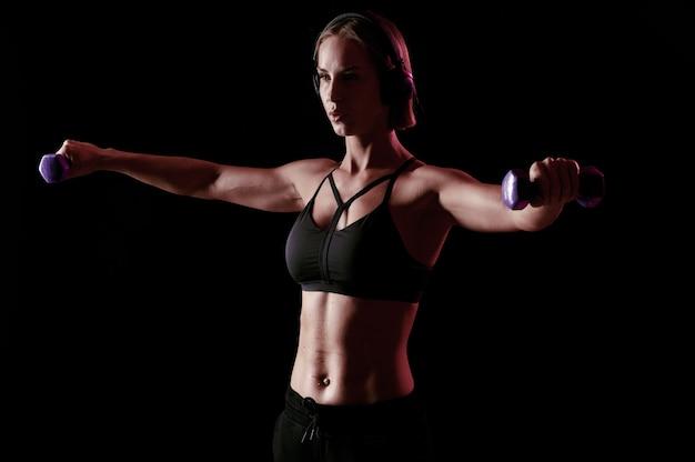 Guarda questa donna muscolosa dal corpo forte e perfetto con manubri e cuffie che si allena al chiuso