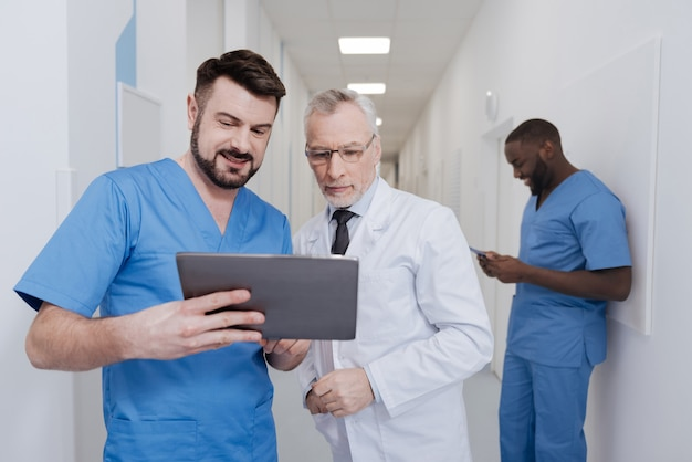 Guarda questa innovazione tecnica. medici competenti competenti coinvolti in piedi nella clinica e tablet di prova mentre altri colleghi utilizzano la cartella in background