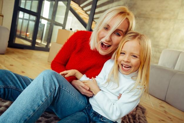 Guardaci. affascinante giovane madre che mantiene il sorriso sul viso mentre abbraccia sua figlia