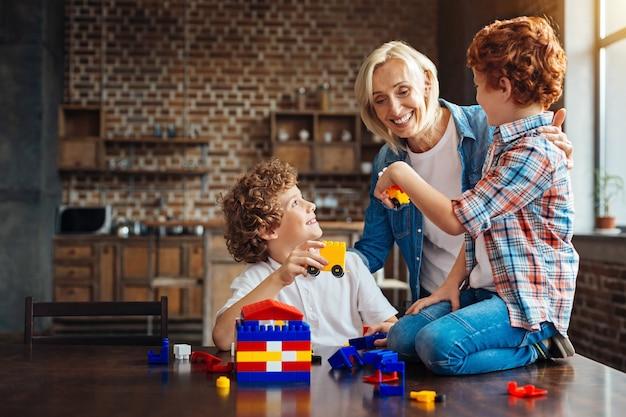 Guarda cosa abbiamo costruito. gioiosa signora anziana che sorride ampiamente mentre abbraccia i suoi nipoti mentre giocano con un set di costruzioni e mostrano le sue auto costruite da loro stessi.