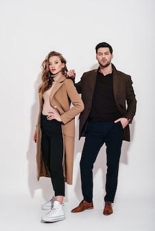 Sembra incredibile coppia attraente e ben vestita in posa in studio