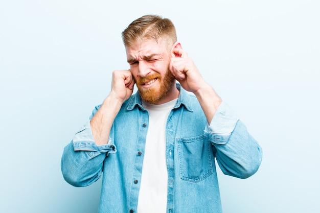 Sembrare arrabbiato, stressato e infastidito, coprendo entrambe le orecchie con un suono assordante, suono o musica ad alto volume