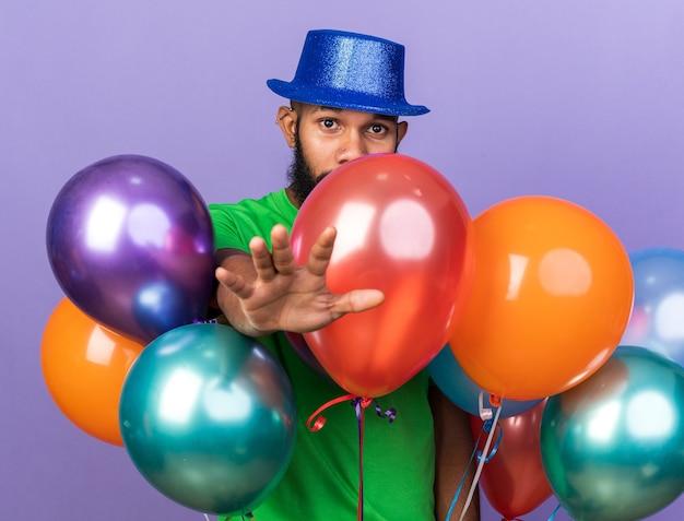 Guardando la telecamera giovane ragazzo afro-americano che indossa un cappello da festa in piedi dietro i palloncini che tengono la mano davanti isolata sul muro blu