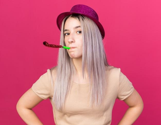Guardando la telecamera giovane bella ragazza che indossa il cappello da festa che soffia il fischio della festa mettendo le mani sull'anca